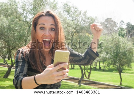 Overjoyed crazy lady with mobile phone getting great news. Happy woman holding smartphone, raising fist in victory gesture, looking at camera and shouting with joy. Communication or joy concept #1403483381