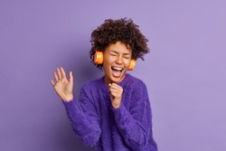Overjoyed dark skinned African American woman sings favorite song has fun listens audio track via headphones dressed in warm sweater isolated over purple background enjoys loud tune or melody