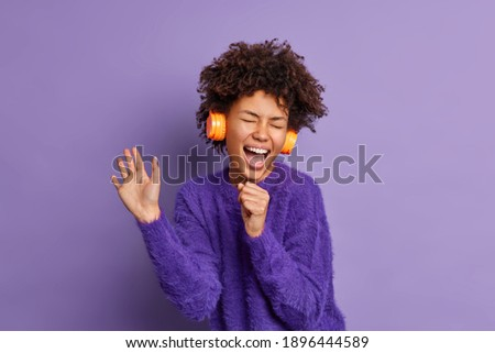 Overjoyed dark skinned African American woman sings favorite song has fun listens audio track via headphones dressed in warm sweater isolated over purple background enjoys loud tune or melody Stock photo ©