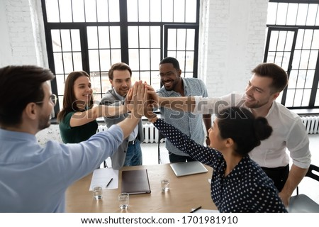 Overjoyed diverse businesspeople give high five celebrate shared victory or win at meeting, excited multiracial colleagues feel motivated engaged in teambuilding activity at briefing in office