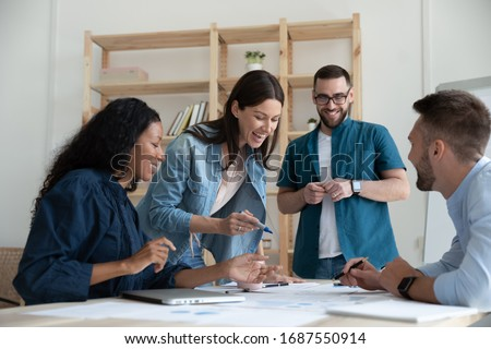 Overjoyed diverse businesspeople have fun engaged in creative thinking at team briefing in office, smiling multiracial colleagues laugh brainstorm discussing ideas at meeting, teamwork concept