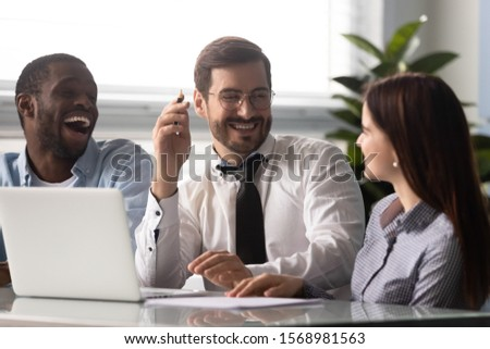 Overjoyed diverse millennial colleagues have fun laugh cooperating at financial project on computer, excited multiethnic coworkers smile at funny joke briefing or brainstorming in casual office