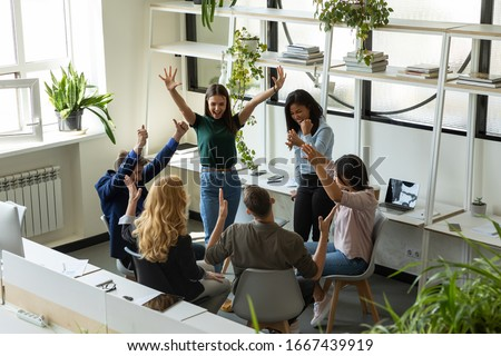 Overjoyed diverse multiethnic businesspeople have fun celebrate shared group achievement in office, excited multiracial colleagues engaged in teambuilding activity, motivated for results at briefing ストックフォト ©