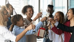 Overjoyed diverse multiracial businesspeople have fun celebrate employee birthday clink glasses in office. Happy multiethnic colleagues laugh have celebration cheers at party at workplace together.