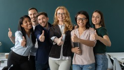 Overjoyed diverse multiracial colleagues stand look at camera recommending good service in office, happy multiethnic employees students show thumb up give recommendation of school or project