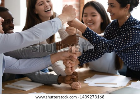 Overjoyed diverse multiracial young people stack fists engaged in funny teambuilding activity at group meeting, excited multiethnic students build strong cooperation show unity support at gathering