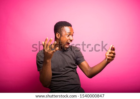 Overjoyed excited back African man glad to recieve text message informing about salary, rejoices good news, stares at mobile phone, gestures actively from happiness, standing  alone. Reaction concept