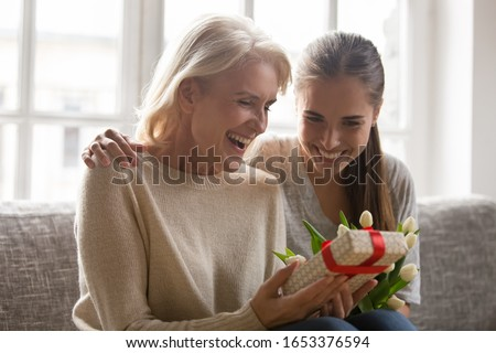 Overjoyed excited curious mature woman sitting with bonding grown up happy smiling daughter on sofa, holding looking at unexpected surprise, wrapped gift box, trying guess what's inside head shot.