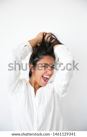 Overjoyed excited woman rejoicing at good news and having fun. Happy young Latin woman in white shirt holding hair overhead, smiling and shouting for joy. Joy concept