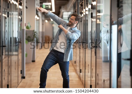 Photo of Overjoyed funny male employee have fun perform winner dance in modern office hallway, excited happy millennial businessman celebrate business success or promotion, Friday evening, end of working week