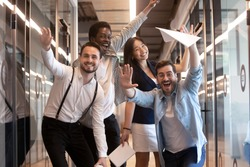 Overjoyed funny multiracial millennial employees look at camera having fun in office hallway, happy excited multiethnic diverse work group, young motivated team posing for picture in corridor