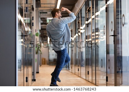 Overjoyed funny young business man jumping in hallway celebrate success victory win reward, happy excited male employee rejoice promotion work well done on friday yes gesture dancing alone in office