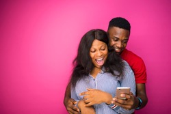overjoyed happy african boyfriend and girlfriend holding modern mobile phone excited to receive text message informing about salary standing indoor on a pink wall. reaction concept