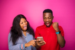 overjoyed happy african couple holds modern mobile phone excited to receive text message informing about salary standing indoor on a pink wall. reaction concept