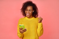 Overjoyed happy excited female glad to receive text message informing about salary, rejoices good news, stares at mobile phone, clenches fists with happiness, celebrates her success. Reaction concept.