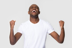 Overjoyed happy young african american man triumphant celebrating lottery betting win screaming with joy isolated on white blank studio background, excited black guy winner rejoicing success victory