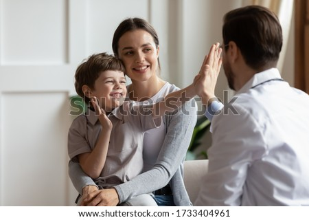 Overjoyed little boy patient have fun give high five to male doctor at consultation in clinic with mom, happy small child greeting with man pediatrician at checkup in hospital, healthcare concept