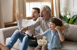 Overjoyed little boy with father and grandfather celebrating goal, sitting on couch with popcorn and soccer ball, excited happy three generations of men watching tv, supporting favorite football team