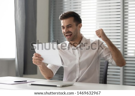 Overjoyed male employee sit at workplace feel euphoric receive post letter with great amazing news, excited man worker triumph read paperwork correspondence stunned get promoted. Success concept