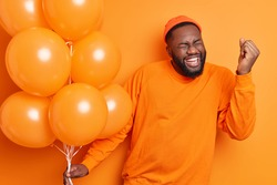 Overjoyed male student celebrates success makes yes gesture being on graduation party holds inflated balloons dressed in casual jumper isolated over orange background. People happiness concept