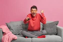 Overjoyed man football fan watches match raises clenched fist and celebrates goal of favorite team holds remote control poses on sofa with cushions around. People pastime and entertainment concept