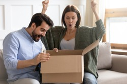 Overjoyed married couple opening carton parcel, excited by received present from international store. Happy emotional clients looking inside cardboard box, surprised by gift, feeling amazed at home.