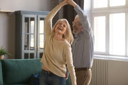 Overjoyed mature grey-haired Caucasian husband and wife have fun enjoy time together at home, happy elderly couple spouses dancing in living room, senior man lead sway smiling middle-aged woman