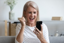 Overjoyed mature old woman hold phone looking at screen feel excited about mobile online app bid win, happy middle aged lady winner celebrate victory success read message good news in cell at home