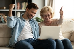 Overjoyed mature woman and young man looking at laptop screen, reading good news in email, showing yes gesture, elderly mother and adult son using computer together, celebrating online lottery win