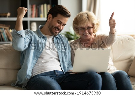 Overjoyed mature woman and young man looking at laptop screen, reading good news in email, showing yes gesture, elderly mother and adult son using computer together, celebrating online lottery win Photo stock ©
