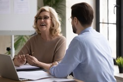 Overjoyed middle aged senior female leader having fun, enjoying informal conversation with young male colleague at office meeting. Happy mature mentor laughing at funny joke with partner indoors.