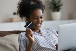 Overjoyed millennial African American woman have fun shopping online with credit card on laptop. Excited young biracial female buy pay on internet on computer at home use good banking secure system.