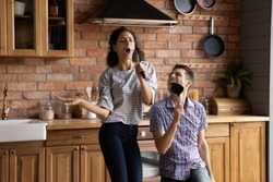 Overjoyed millennial Caucasian man and woman have fun dancing singing in modern kitchen at home. Excited happy young couple feel playful enjoy good morning in new own house or flat. Rental concept.