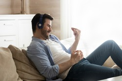 Overjoyed millennial Caucasian man relax on comfortable couch in living room have fun enjoy good quality sound in earphones, happy young male play imaginary guitar dance listen to music in headphones