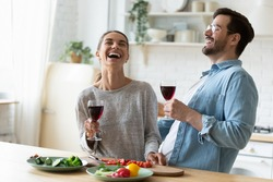 Overjoyed millennial couple drink wine cook together in kitchen have fun joking enjoy weekend at home, happy excited young husband and wife laugh celebrate wedding anniversary or having date