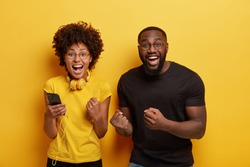 Overjoyed millennial dark skinned woman and man dance and clench fists from joy, listen music on cell phone, enjoy favourite playlist have fun together, use modern headphones, isolated over yellow