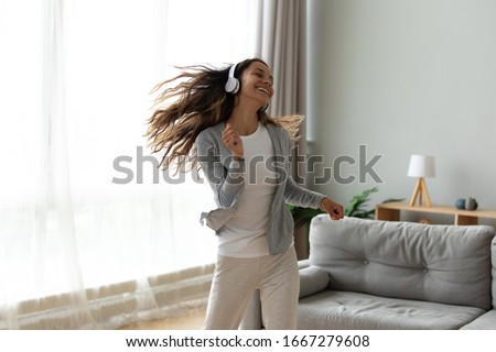 Photo of Overjoyed millennial girl wearing headphones have fun moving listening to music relax in living room, happy young woman in earphones dance enjoy leisure weekend at home, stress free concept