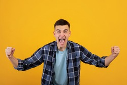 Overjoyed millennial guy screaming in excitement, gesturing YES with both hands on orange studio background. Triumphant young man in casual wear shouting WOW, celebrating his success