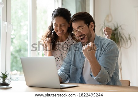 Overjoyed millennial man and woman triumph win online lottery on laptop. Happy excited young Caucasian couple feel euphoric with good email, get amazing sale offer or discount deal on computer.