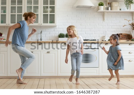 Overjoyed millennial mom or nanny dancing with little girls children in white modern kitchen, happy young Caucasian mother have fun involved in activity together with small daughters at home