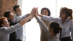 Overjoyed multi racial businesspeople succeed goal giving high five feels excited. Successful corporate team congratulating each other with victory achievement hold hands together show spirit of unity