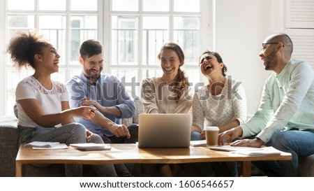 Overjoyed multiethnic millennial diverse students sit at desk have fun studying together using laptop, excited happy international young people laugh and joke engaged in teamwork preparing for test