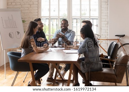Overjoyed multiethnic young businesspeople sit at meeting talk chat brainstorm in boardroom together, smiling diverse colleagues speak discussing business ideas, laugh in casual office atmosphere