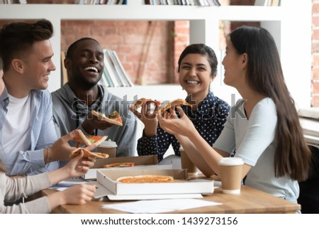 Overjoyed multiethnic young people sit at desk talk joking and eating pizza together, happy diverse students have fun chatting and laughing during break tasting enjoying Italian fast food