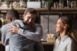 Overjoyed multiracial male friends embrace meeting hanging out in restaurant, happy diverse young people hug reunited gathering in bar having fun chilling together laughing and relaxing outdoors