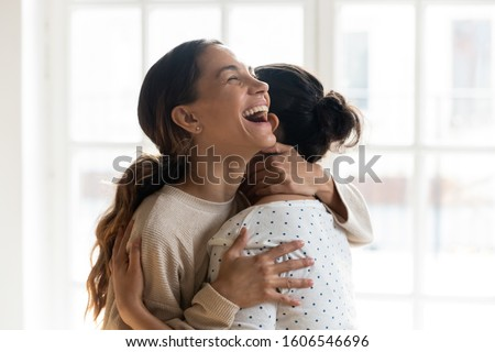 Overjoyed multiracial young female friends excited to meet hug cuddle laughing and joking, happy multiethnic millennial girls smile embracing show love and unity, friendship, reunion concept
