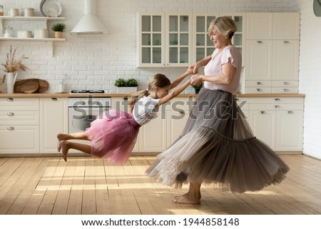 Overjoyed optimistic mature 60s grandmother and little 8s granddaughter wear princess skirts dresses dance together in kitchen. Happy elderly granny have fun play enjoy weekend with small grandchild.