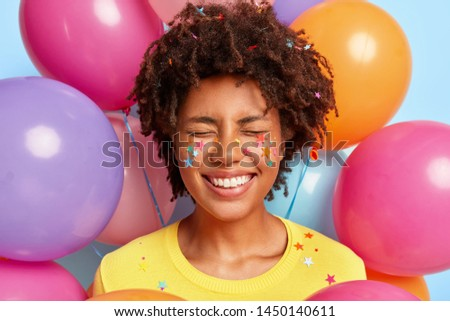 Overjoyed pleased woman with Afro hairstyle, smiles broadly, expresses positive emotions, has decorative colorful stars on face and hair, stands against air balloons. People, joy, holiday concept