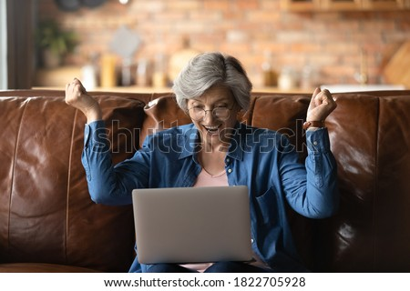 Overjoyed senior Caucasian grandmother in glasses relax on sofa at home triumph reading good news on laptop, excited elderly 60s woman feel euphoric win online lottery on computer, luck concept Foto d'archivio ©