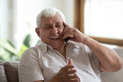 Overjoyed senior 80s grandfather sit on sofa at home laugh talking on modern cellphone, happy mature 70s man relax in living room speak have pleasant smartphone call, elderly and technology concept